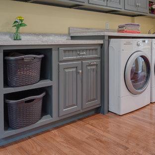 Foto di una lavanderia multiuso tradizionale con lavello da incasso, ante grigie, pavimento in legno massello medio, lavatrice e asciugatrice affiancate, ante con bugna sagomata e pareti beige