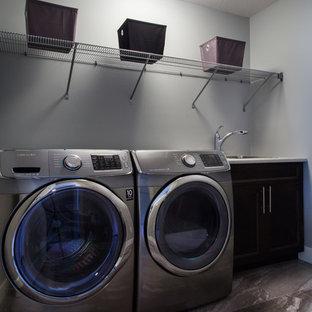 Esempio di una piccola sala lavanderia minimal con lavello a vasca singola, ante in stile shaker, ante in legno bruno, top in laminato, pareti grigie, pavimento con piastrelle in ceramica e lavatrice e asciugatrice affiancate