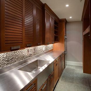 Foto på en funkis grå parallell tvättstuga, med luckor med lamellpanel, skåp i mörkt trä och bänkskiva i rostfritt stål
