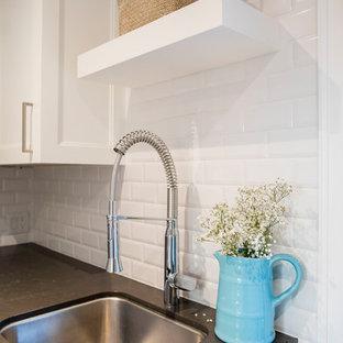 Klassisk inredning av ett mellanstort grå l-format grått grovkök, med en undermonterad diskho, skåp i shakerstil, vita skåp, bänkskiva i onyx, blå väggar, klinkergolv i porslin, en tvättmaskin och torktumlare bredvid varandra och grått golv