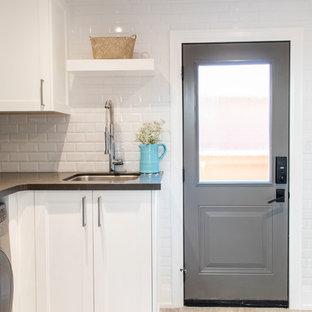 Bild på ett mellanstort vintage grå l-format grått grovkök, med en undermonterad diskho, skåp i shakerstil, vita skåp, bänkskiva i onyx, blå väggar, klinkergolv i porslin, en tvättmaskin och torktumlare bredvid varandra och grått golv