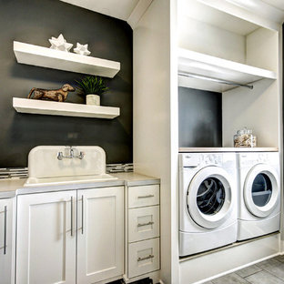 Foto på en vintage tvättstuga, med en nedsänkt diskho, skåp i shakerstil, vita skåp, svarta väggar och en tvättmaskin och torktumlare bredvid varandra