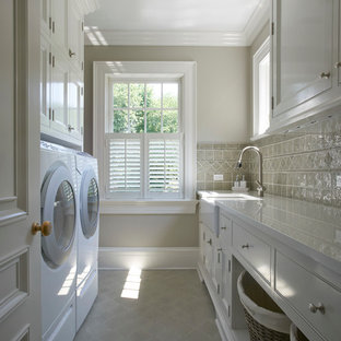 This is an example of a mid-sized traditional galley dedicated laundry room in New York with white cabinets, a farmhouse sink, solid surface benchtops, ceramic floors, a side-by-side washer and dryer, grey floor, white benchtop, beaded inset cabinets and grey walls.