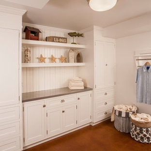 Large traditional u-shaped utility room in Seattle with a farmhouse sink, white cabinets, zinc benchtops, concrete floors, a side-by-side washer and dryer and flat-panel cabinets.