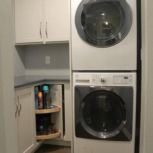 Exempel på en liten klassisk blå l-formad blått tvättstuga enbart för tvätt, med skåp i shakerstil, bänkskiva i kvarts, vitt stänkskydd, stänkskydd i keramik, vinylgolv, brunt golv, grå skåp, blå väggar och en tvättpelare