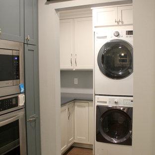 Idéer för en liten klassisk blå l-formad tvättstuga enbart för tvätt, med skåp i shakerstil, bänkskiva i kvarts, vitt stänkskydd, stänkskydd i keramik, vinylgolv, brunt golv, grå skåp, blå väggar och en tvättpelare