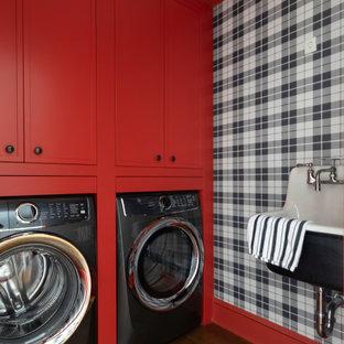 Aménagement d'une buanderie classique dédiée avec un placard avec porte à panneau encastré, des portes de placard rouges, un mur multicolore, un sol en bois foncé, des machines côte à côte et du papier peint.