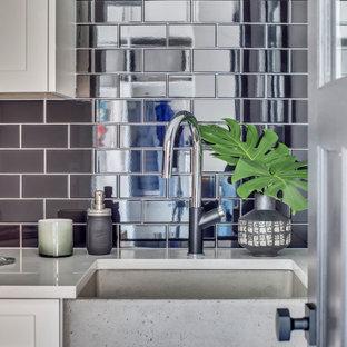 Bild på en lantlig vita vitt tvättstuga, med en rustik diskho, bänkskiva i kvartsit, svart stänkskydd, stänkskydd i porslinskakel och en tvättpelare