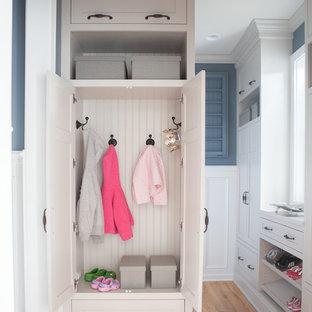 Idee per una piccola lavanderia multiuso chic con lavello stile country, ante con riquadro incassato, ante bianche, pareti blu, pavimento in legno massello medio e lavatrice e asciugatrice affiancate