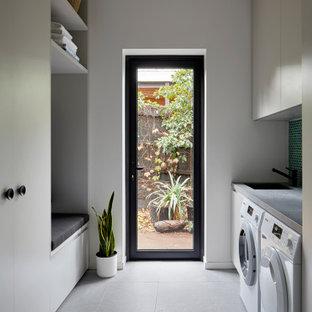 Exempel på en stor modern grå parallell grått tvättstuga enbart för tvätt, med en nedsänkt diskho, släta luckor, vita skåp, grönt stänkskydd, stänkskydd i mosaik, vita väggar, klinkergolv i porslin, en tvättmaskin och torktumlare bredvid varandra och grått golv