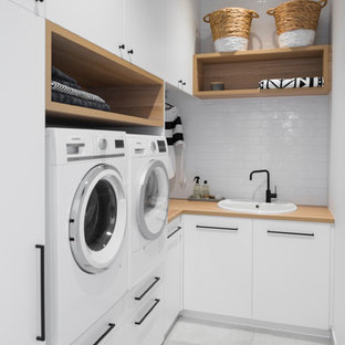 Photo of a small beach style l-shaped dedicated laundry room in Adelaide with a drop-in sink, white cabinets, wood benchtops, white walls, ceramic floors, a side-by-side washer and dryer, brown benchtop, flat-panel cabinets and grey floor.