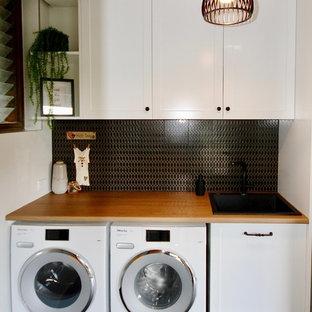 Esempio di una piccola sala lavanderia shabby-chic style con lavello da incasso, ante in stile shaker, ante bianche, top in legno, pareti bianche, pavimento con piastrelle in ceramica, lavatrice e asciugatrice affiancate e pavimento nero