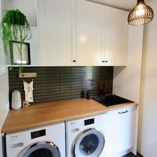 Idéer för små shabby chic-inspirerade linjära tvättstugor enbart för tvätt, med en nedsänkt diskho, skåp i shakerstil, vita skåp, träbänkskiva, vita väggar, klinkergolv i keramik, en tvättmaskin och torktumlare bredvid varandra och svart golv