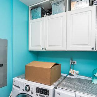 Idéer för mellanstora funkis linjära tvättstugor enbart för tvätt, med blå väggar, en tvättmaskin och torktumlare bredvid varandra och blått golv