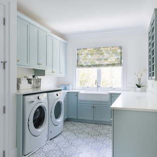 Inspiration for a beach style u-shaped multicolored floor dedicated laundry room remodel in Chicago with a farmhouse sink, shaker cabinets, blue cabinets, white walls and white countertops