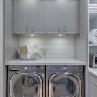 Photo of a small contemporary single-wall utility room in Vancouver with flat-panel cabinets, grey cabinets, grey splashback, light hardwood floors, a side-by-side washer and dryer, beige floor, white benchtop and planked wall panelling.