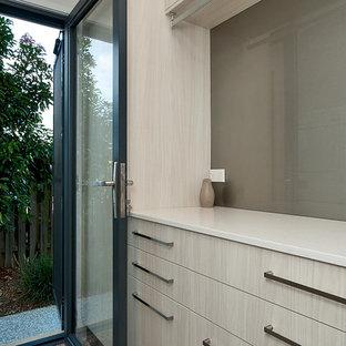 Exemple d'une petite buanderie parallèle moderne dédiée avec un évier encastré, un placard à porte plane, des portes de placard en bois clair, un plan de travail en quartz modifié, un mur blanc, un sol en carrelage de céramique et des machines superposées.