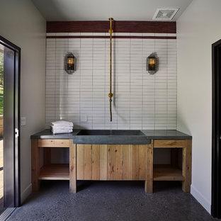 Exempel på en lantlig tvättstuga, med en integrerad diskho, öppna hyllor, skåp i ljust trä, bänkskiva i betong, vita väggar och grått golv