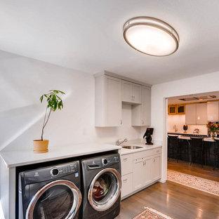 Idéer för att renovera en mellanstor funkis u-formad tvättstuga enbart för tvätt, med luckor med upphöjd panel, beige skåp, bänkskiva i kvarts, vita väggar, ljust trägolv, en tvättmaskin och torktumlare bredvid varandra, beiget golv och en undermonterad diskho