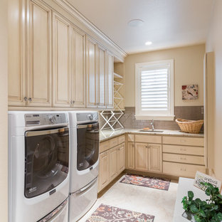 This is an example of a large rustic l-shaped separated utility room in Denver with a submerged sink, raised-panel cabinets, white cabinets, granite worktops, beige walls, a side by side washer and dryer, porcelain flooring, beige floors and beige worktops.