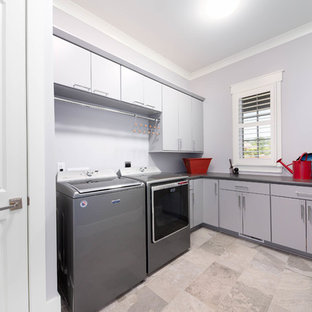 This is an example of a large traditional l-shaped separated utility room in Other with flat-panel cabinets, grey cabinets, laminate countertops, grey walls, ceramic flooring, a side by side washer and dryer, green floors and grey worktops.