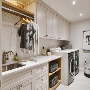 Inspiration för en stor vintage vita vitt tvättstuga enbart för tvätt, med en undermonterad diskho, skåp i shakerstil, grå skåp, bänkskiva i kvartsit, vita väggar, klinkergolv i porslin, en tvättmaskin och torktumlare bredvid varandra och grått golv