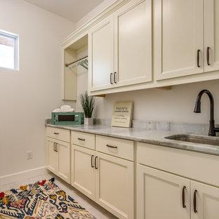 タンパの中くらいのトランジショナルスタイルのおしゃれな洗濯室 (I型、アンダーカウンターシンク、落し込みパネル扉のキャビネット、白いキャビネット、オニキスカウンター、白い壁、磁器タイルの床) の写真