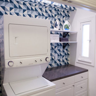 Inspiration for a medium sized contemporary galley laundry cupboard in San Francisco with flat-panel cabinets, white cabinets, engineered stone countertops, multi-coloured walls, a stacked washer and dryer and black worktops.