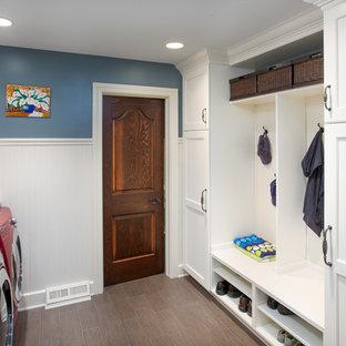 Inredning av ett klassiskt mellanstort linjärt grovkök, med luckor med infälld panel, vita skåp, marmorbänkskiva, beige väggar, klinkergolv i porslin, en tvättmaskin och torktumlare bredvid varandra och beiget golv