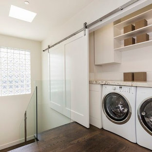 This is an example of a small arts and crafts single-wall laundry cupboard in San Francisco with white cabinets, granite benchtops, a side-by-side washer and dryer, flat-panel cabinets, beige walls, dark hardwood floors and brown floor.
