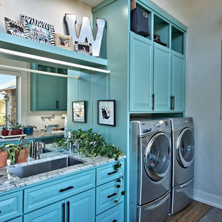 Design ideas for a large traditional galley utility room in Austin with a submerged sink, raised-panel cabinets, blue cabinets, marble worktops, grey walls, dark hardwood flooring and a side by side washer and dryer.