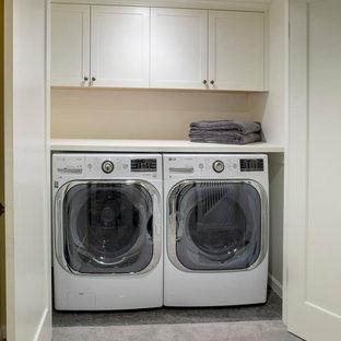 Foto på en liten amerikansk linjär liten tvättstuga, med skåp i shakerstil, vita skåp, träbänkskiva, betonggolv, en tvättmaskin och torktumlare bredvid varandra och beige väggar