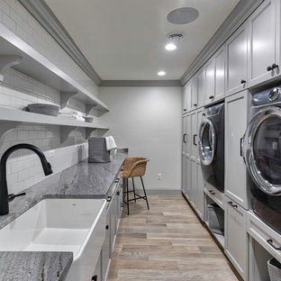 Example of a large transitional galley light wood floor and beige floor dedicated laundry room design in Detroit with a farmhouse sink, recessed-panel cabinets, gray cabinets, white walls, an integrated washer/dryer, gray countertops and granite countertops