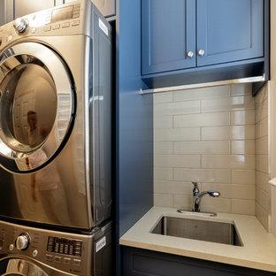 Idee per una sala lavanderia tradizionale di medie dimensioni con ante in stile shaker, ante blu, top in quarzite, pareti beige, pavimento in gres porcellanato, lavatrice e asciugatrice a colonna, pavimento beige e top beige