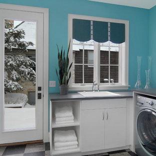 Immagine di una lavanderia minimal con ante bianche, pavimento grigio e top grigio