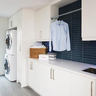 Стильный дизайн: линейная универсальная комната среднего размера в скандинавском стиле с врезной раковиной, плоскими фасадами, белыми фасадами, столешницей из кварцита, белыми стенами, полом из керамогранита и с сушильной машиной на стиральной машине - последний тренд