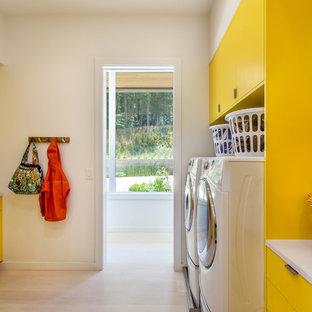 Inspiration för en funkis parallell tvättstuga enbart för tvätt, med släta luckor, gula skåp, bänkskiva i kvarts, vita väggar, en tvättmaskin och torktumlare bredvid varandra och ljust trägolv