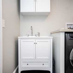 Mid-sized transitional single-wall vinyl floor and gray floor dedicated laundry room photo in Boston with a drop-in sink, recessed-panel cabinets, white cabinets, laminate countertops, gray walls, a side-by-side washer/dryer and brown countertops