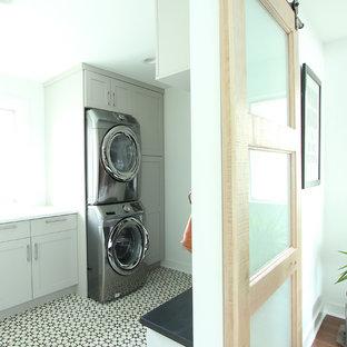 Idéer för att renovera en liten vintage linjär tvättstuga enbart för tvätt, med luckor med infälld panel, grå skåp, bänkskiva i kvarts, vita väggar, klinkergolv i porslin, en tvättpelare och flerfärgat golv
