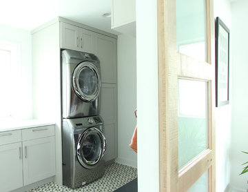 Grey Painted Cabinets in Laundry Room with Stacked Washer and Dryer