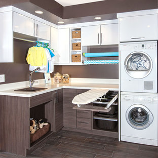 Example of a mid-sized trendy l-shaped porcelain floor utility room design in Minneapolis with a drop-in sink, flat-panel cabinets, white cabinets, laminate countertops, brown walls and a stacked washer/dryer