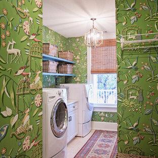 Bild på en mellanstor vintage linjär tvättstuga enbart för tvätt, med en tvättmaskin och torktumlare bredvid varandra, beiget golv, luckor med upphöjd panel, vita skåp, flerfärgade väggar och travertin golv