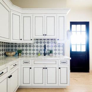 Foto di una lavanderia multiuso mediterranea di medie dimensioni con lavello sottopiano, ante in stile shaker, ante bianche, top in marmo, pareti beige, lavatrice e asciugatrice affiancate, pavimento beige, parquet chiaro e top bianco