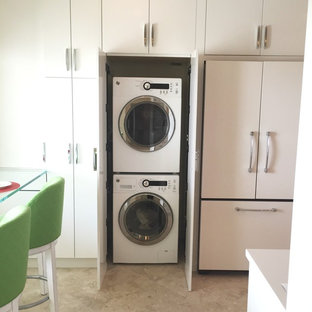 Inspiration for a modern laundry room remodel in Miami with white cabinets and a stacked washer/dryer