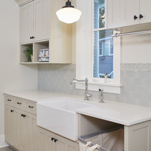 Example of a country single-wall brown floor dedicated laundry room design in Grand Rapids with a farmhouse sink, shaker cabinets, beige cabinets, white countertops, solid surface countertops and gray walls