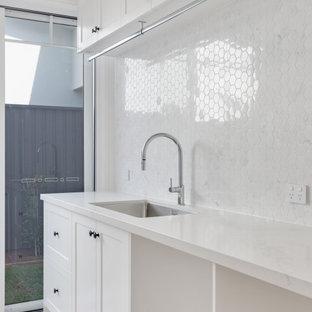 Idéer för att renovera en stor maritim vita parallell vitt tvättstuga enbart för tvätt, med en undermonterad diskho, skåp i shakerstil, vita skåp, marmorbänkskiva, vitt stänkskydd, stänkskydd i marmor, vita väggar, ljust trägolv, en tvättmaskin och torktumlare bredvid varandra och brunt golv