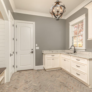 Mid-sized elegant u-shaped brick floor utility room photo in Other with an undermount sink, recessed-panel cabinets, beige cabinets, granite countertops and gray walls