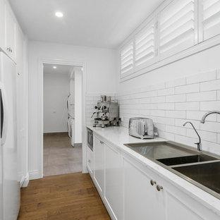 Exempel på en stor klassisk gula parallell gult tvättstuga, med en undermonterad diskho, skåp i shakerstil, vita skåp, bänkskiva i kvarts, vitt stänkskydd, stänkskydd i tunnelbanekakel, linoleumgolv och brunt golv