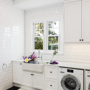 This is an example of a beach style single-wall dedicated laundry room in Gold Coast - Tweed with recessed-panel cabinets, white cabinets, white benchtop, a farmhouse sink, white walls, a side-by-side washer and dryer and multi-coloured floor.