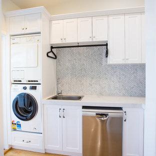 Inredning av ett modernt litet vit l-format vitt grovkök, med en enkel diskho, skåp i shakerstil, vita skåp, bänkskiva i kvarts, vita väggar, mellanmörkt trägolv, en tvättpelare och brunt golv